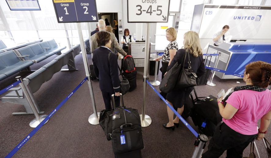 Passengers wait at a United Airlines gate to board a flight at O'Hare International Airport in Chicago. (AP Photo/M. Spencer Green)