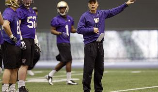 New Washington head football coach Chris Petersen, right, gives directions to his team on the first day of spring NCAA college football practice, Tuesday, March 4, 2014, in Seattle. (AP Photo/Ted S. Warren)