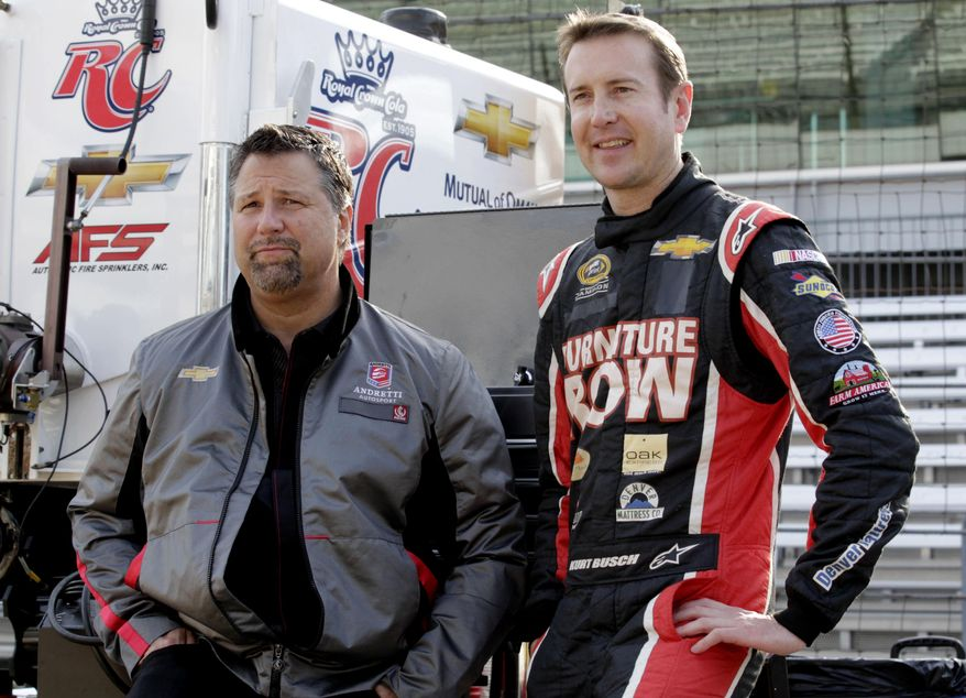 FILE - In this May 9, 2013 file photo, Andretti Autosport team owner Michael Andretti, left, and NASCAR driver Kurt Busch wait for the start of a testing session at the Indianapolis Motor Speedway in Indianapolis. Kurt Busch and Andretti Autosport announced Tuesday, March 4, 2014, that he will try to become the first driver in 10 years to run the Indianapolis 500 and the Coca-Cola 600 on the same day.  (AP Photo/AJ Mast, File)