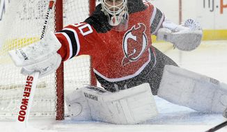 New Jersey Devils goaltender Martin Brodeur deflects the puck during the first period of an NHL hockey game against the Detroit Red Wings Tuesday, March 4, 2014, in Newark, N.J. (AP Photo/Bill Kostroun)