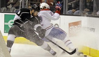 Montreal Canadiens right winger Dale Weise (22) and Los Angeles Kings defenseman Jake Muzzin (6) battle in the first period of an NHL hockey game in Los Angeles Monday, March 3, 2014. (AP Photo/Reed Saxon)