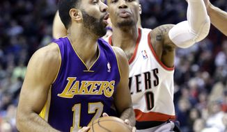 Los Angeles Lakers guard Kendall Marshall, left, looks to shoot against Portland Trail Blazers guard Damian Lillard during the first half of an NBA basketball game in Portland, Ore., Monday, March 3, 2014. (AP Photo/Don Ryan)