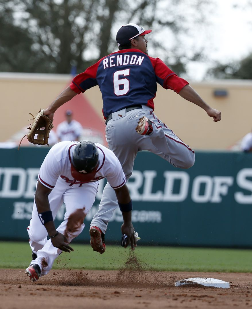 Washington Nationals second baseman Anthony Rendon (6) jumps over Atlanta Braves' Justin Upton (8) after getting the out at second and throwing to first base to complete the double play in the second inning of a spring exhibition baseball game, Tuesday, March 4, 2014, in Kissimmee, Fla. (AP Photo/Alex Brandon)