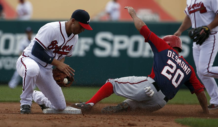 Washington Nationals' Ian Desmond (20) is safe at second base on the steal as Atlanta Braves shortstop Andrelton Simmons bobbles the throw, in the fourth inning of a spring exhibition baseball game, Tuesday, March 4, 2014, in Kissimmee, Fla. (AP Photo/Alex Brandon)