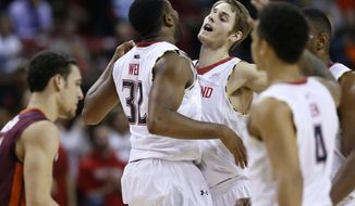 Maryland guard Dez Wells (32) chest-bumps teammate Jake Layman during a timeout in the second half of an NCAA college basketball game against Virginia Tech in College Park, Md., Tuesday, March 4, 2014. Maryland won 64-47. (AP Photo/Patrick Semansky)