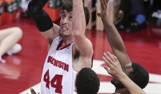 Wisconsin's Frank Kaminsky (44) shoots against Purdue's A.J. Hammons (20) and Errick Peck during the first half of an NCAA college basketball game Wednesday, March 5, 2014, in Madison, Wis. (AP Photo/Andy Manis)