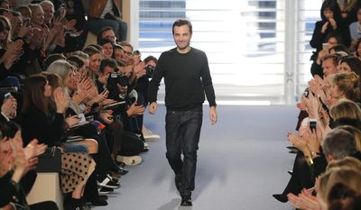 French creative director  Nicolas Ghesquiere acknowledges applause after the presentation of Louis Vuitton's ready to wear fall/winter 2014-2015 fashion collection, in Paris, Wednesday, March 5, 2014. (AP Photo/Jacques Brinon)