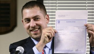 Sean Green displays his new Washington state legal marijuana license at a presentation Wednesday, March 5, 2014, in Olympia, Wash. Green, a medical marijuana dispensary operator from Spokane, was issued the producer-processor license under the state's recreational pot law at the Liquor Control Board meeting. (AP Photo/Elaine Thompson)