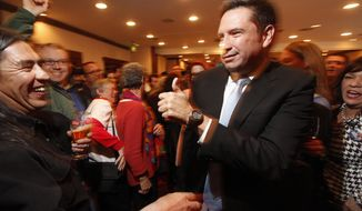 Mayor elect Javier Gonzales greets people as he makes his way to address his supporters at Hotel Santa Fe Tuesday March 4, 2014. (AP Photo/The Santa Fe New Mexican, Luis Sanchez Saturno)