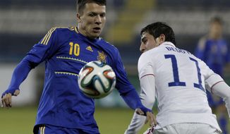 Yevhen Konoplianka, left, of Ukraine controls the ball with Alejandro Bedoya of U.S. during an international friendly match at Antonis Papadopoulos stadium in southern city of Larnaca, Cyprus, Wednesday, March 5, 2014.  The Ukrainians are facing the United States in a friendly on Wednesday in Cyprus, a match moved from Kharkiv to Larnaca for security reasons. (AP Photo/Petros Karadjias)