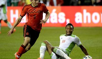 Mexico's Hector Herrera (8) charges for the ball around Nigeria's John Obi Mikel (10) during the first half of an international friendly soccer match Wednesday, March 5, 2014, in Atlanta. (AP Photo/David Tulis)