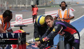 Formula One driver Sebastian Vettel of Red Bull Racing helps push his car after breaking down during pre-season testing at the Bahrain International Circuit in Sakhir, Bahrain, Saturday, March 1, 2014. (AP Photo/Hasan Jamali)