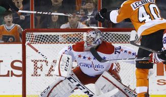 Philadelphia Flyers' Vincent Lecavalier, right, tries to knock the puck past Washington Capitals' Braden Holtby during the first period of an NHL hockey game, Wednesday, March 5, 2014, in Philadelphia. (AP Photo/Matt Slocum)