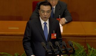 Chinese Premier Li Keqiang delivers a work report during the opening session of the annual National People's Congress in Beijing's Great Hall of the People, China, Wednesday, March 5, 2014. (AP Photo/Ng Han Guan)