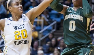 FILE - In this Jan. 8, 2014 file photo, West Virginia's Asya Bussie, left, blocks Baylor's Odyssey Sims during the second half of an NCAA college basketball game in Morgantown, W.Va.  Bussie and others could have a big impact on which teams win their league titles. (AP Photo/Andrew Ferguson, File)