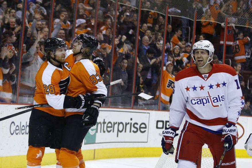 Philadelphia Flyers' Claude Giroux, left, celebrates with Jakub Voracek as Washington Capitals' Eric Fehr skates by after Giroux's goal during the second period of an NHL hockey game, Wednesday, March 5, 2014, in Philadelphia. (AP Photo/Matt Slocum)