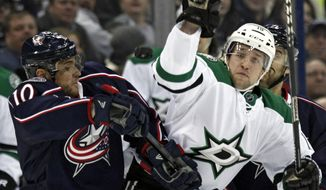 Columbus Blue Jackets' Marian Gaborik, left, of Slovakia, and Dallas Stars' Chris Mueller work for the puck in the first period of an NHL hockey game in Columbus, Ohio, Tuesday, March 4, 2014. (AP Photo/Paul Vernon)
