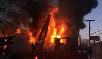 Firefighters battle a four-alarm fire at a three-story apartment complex Wednesday morning, March 5, 2014 on Detroit's west side. An official says the fire forced some people to jump to escape. (AP Photo/Detroit Free Press, Robert Allen)  DETROIT NEWS OUT;  NO SALES