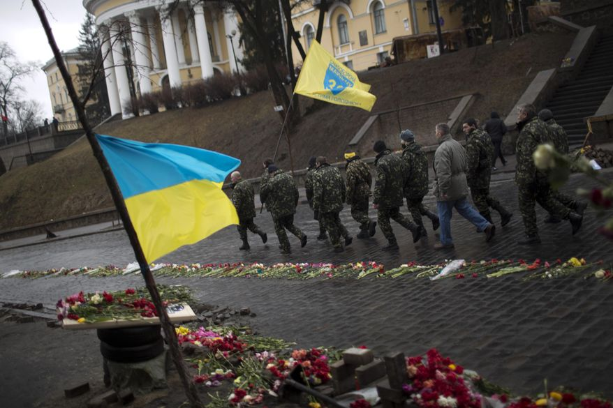 """Ukrainian men wearing camouflage uniforms march along a street at a memorial for people killed during clashes with police at Kiev's Independence Square, Ukraine, Wednesday, March 5, 2014. Stepping back from the brink of war, Vladimir Putin talked tough but cooled tensions in the Ukraine crisis Tuesday, saying Russia has no intention """"to fight the Ukrainian people"""" but reserves the right to use force. As the Russian president held court in his personal residence, U.S. Secretary of State John Kerry met with Kiev's fledgling government and urged Putin to stand down. (AP Photo/Emilio Morenatti)"""