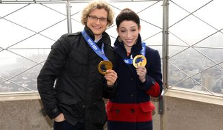 FILE - In this Thursday, Feb. 27, 2014 file photo, Olympic gold medalist ice dancers Meryl Davis and Charlie White, left, visit the Empire State Building in New York. ABC says it will air figure-skating specials with the Sochi Olympic gold medalists Davis and White among the performers. Veteran Olympian Brian Boitano also will skate in the series of four specials hosted by Kristi Yamaguchi and Michael Weiss, ABC said Wednesday, March 5, 2014. (Photo by Evan Agostini/Invision/AP, file)