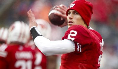 FILE - In this Nov. 16, 2013 file photo, Wisconsin quarterback Joel Stave warms up on the sidelines during the second half of an NCAA college football game against Indiana, in Madison, Wisc. Spring practice opens at Wisconsin, where coach Gary Andersen hopes to see improvement from Stave. (AP Photo/Andy Manis, File)