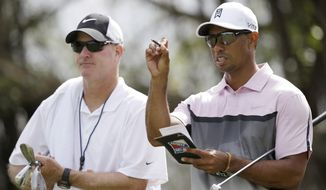 Golfer Tiger Woods, right, and his caddie Joe LaCava look over the fifth hole during a practice round in the Cadillac Championship golf tournament, Wednesday, March 5, 2014, in Doral, Fla. Three days after he withdrew in the middle of the final round at the Honda Classic with lower back pain, Woods returned to work at the Cadillac Championship by saying he feels better after a few days of constant treatment, and that he was good enough to try to defend his title. (AP Photo/Wilfredo Lee)