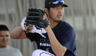 Seattle Mariners pitcher Hisashi Iwakuma of Japan works out with staff in the bullpen using a towel in his throwing hand during a morning workout at spring training baseball practice, Wednesday, March 5, 2014, in Peoria, Ariz. (AP Photo/Tony Gutierrez)