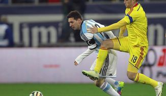 Argentina's Lionel Messi, left, challenges for the ball with Romania's Mihai Pintilii, right, during an international friendly soccer game on the National Arena stadium in Bucharest, Romania, Wednesday, March 5, 2014.. (AP Photo/Vadim Ghirda)