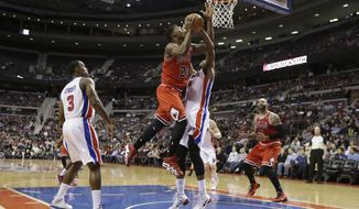 Chicago Bulls guard Jimmy Butler (21) shoots over the defense of Detroit Pistons forward Greg Monroe (10) during the first half of an NBA basketball game in Auburn Hills, Mich., Wednesday, March 5, 2014. (AP Photo/Carlos Osorio)