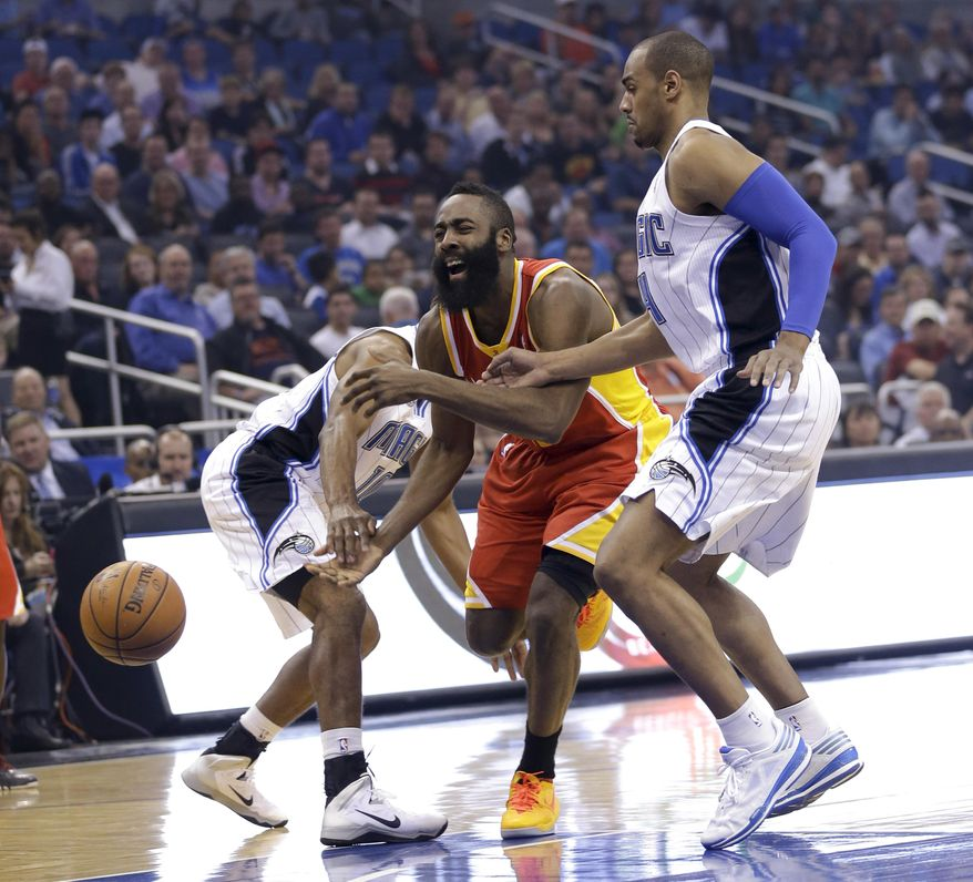 Houston Rockets' James Harden, center, loses control of the ball as he tries to drive between Orlando Magic's Ronnie Price, left, and Arron Afflalo during the first half of an NBA basketball game in Orlando, Fla., Wednesday, March 5, 2014. (AP Photo/John Raoux)