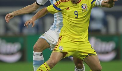 Argentina's Frederico Fernandez, left, challenges with Romania's Ciprian Marica, right, during an international friendly soccer game on the National Arena stadium in Bucharest, Romania, Wednesday, March 5, 2014. (AP Photo/Vadim Ghirda)