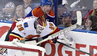 Calgary Flames goalie Reto Berra (29) is hit by Edmonton Oilers' Taylor Hall (4) during third period NHL hockey action in Edmonton, Alberta, on Saturday March 1, 2014.  (AP Photo/The Canadian Press, Jason Franson)