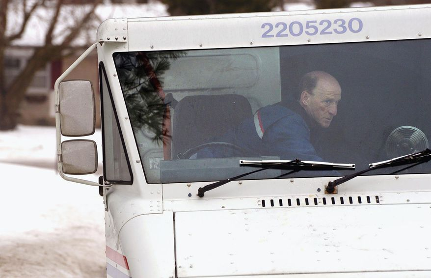 **FILE** U.S. Postal Service letter carrier Gary Keist prepares to deliver mail on his route in Normal, Ill., on Feb. 20, 2014. (Associated Press/The Pantagraph, Steve Smedley)
