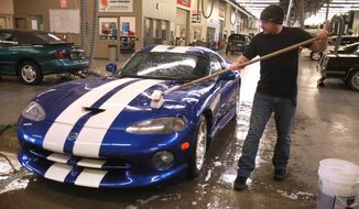 Student Mike Murphy of Yelm, Wash., washes the one-of-a-kind, $250,000 Dodge Viper SRT in the automotive shop at South Puget Sound Community College in Tumwater, Wash., on Tuesday, March 4, 2014. The school received notice Tuesday morning that Chrysler ordered the entire collection of educational Vipers - believed to be about 93 cars worth tens of millions of dollars - to be crushed. (AP Photo/The Olympian, Tony Overman)