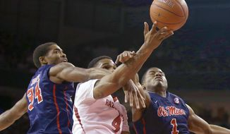Mississippi's Aaron Jones (34) and Martavious Newby (1) try to block a shot by  Arkansas' Coty Clarke (4) in the first half of an NCAA college basketball game in Fayetteville, Ark., Wednesday, March 5, 2014. (AP Photo/Danny Johnston)