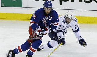 Tampa Bay Lightning's Martin St. Louis (26) fights for control of the puck with New York Rangers' Ryan Callahan (24) during the third period of an NHL hockey game on Thursday, Feb. 28, 2013, in New York. The Rangers won the game 4-1. (AP Photo/Frank Franklin II)