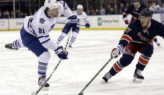Toronto Maple Leafs' Phil Kessel (81) shoots the puck past New York Rangers' Ryan McDonagh (27) during the first period of an NHL hockey game Wednesday, March 5, 2014, in New York. (AP Photo/Frank Franklin II)