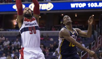 Washington Wizards power forward Drew Gooden (90) scores past Utah Jazz point guard Alec Burks during the first half of an NBA basketball game on Wednesday, March 5, 2014, in Washington. The Wizards defeated the Jazz 104-91. (AP Photo/ Evan Vucci)