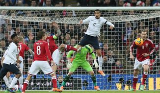 England's Chris Smalling, leaps but fails to connect with the ball during the international friendly soccer match between England and Denmark at Wembley stadium in London Wednesday, March  5,  2014. (AP Photo/Alastair Grant)