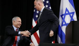 Israeli Prime Minister Benjamin Netanyahu, left, shakes hands with California Gov. Jerry Brown, right, before the signing of an agreement to expand cooperation at the Computer History Museum Wednesday, March 5, 2014, in Mountain View, Calif. Netanyahu is visiting California, trading a focus on the geopolitics of the Middle East for a Hollywood screening and visits with Silicon Valley tech entrepreneurs. (AP Photo/Eric Risberg)