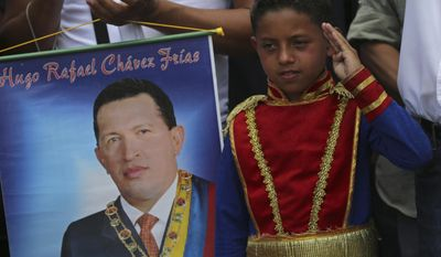 A boy wearing an historical uniform associated with Venezuelan hero Simon Bolivar salutes while standing next to a poster of the late President Hugo Chavez during a military parade commemorating the one year anniversary of Chavez's death, in Caracas, Venezuela, Wednesday, March 5, 2014. The anniversary of Chavez's death was marked with a mix of street protests and solemn commemorations that reflected deep divisions over the Venezuela he left behind. (AP Photo/Fernando Llano)