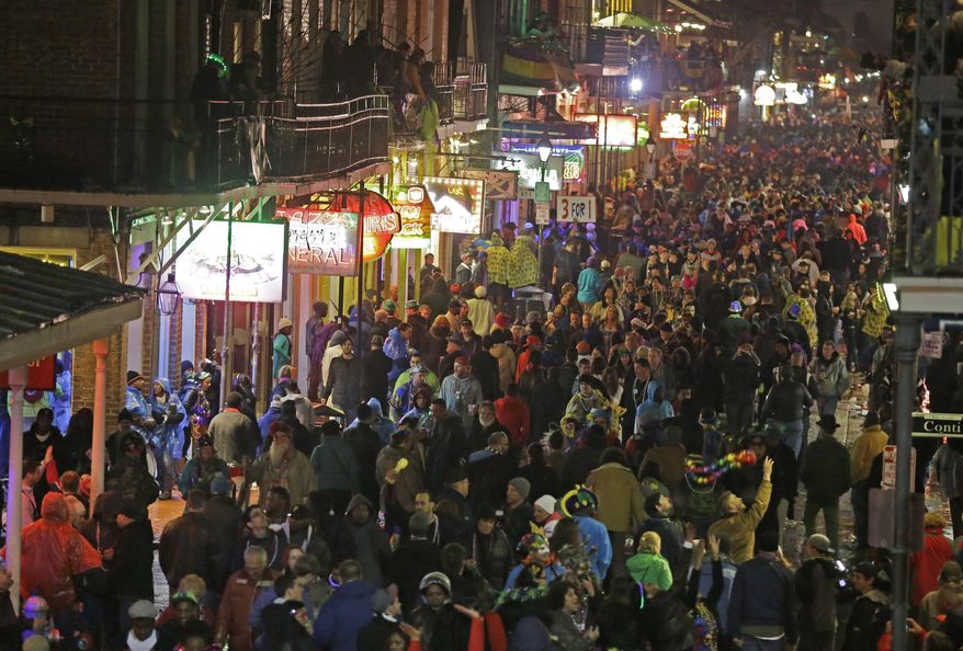 Mardi Gras crowds in the French Quarter are seen from the balcony of the Royal Sonesta Hotel in New Orleans, Tuesday, March 4, 2014. Rain and unusually cold temperatures caused the crowd to be smaller than previous years.  (AP Photo/Gerald Herbert)