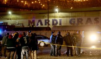 New Orleans Police investigate a double homicide in the parking lot in front of Mardi Gras World in New Orleans on Tuesday, March 4, 2014. (AP Photo/The Times-Picayune, Michael DeMocker)