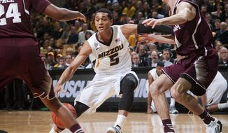 Missouri's Jordan Clarkson, center, tries to split Texas A&M's Alex Caruso, right, and Antwan Space, left, on a drive during the first half of an NCAA college basketball game Wednesday, March 5, 2014, in Columbia, Mo. (AP Photo/L.G. Patterson)