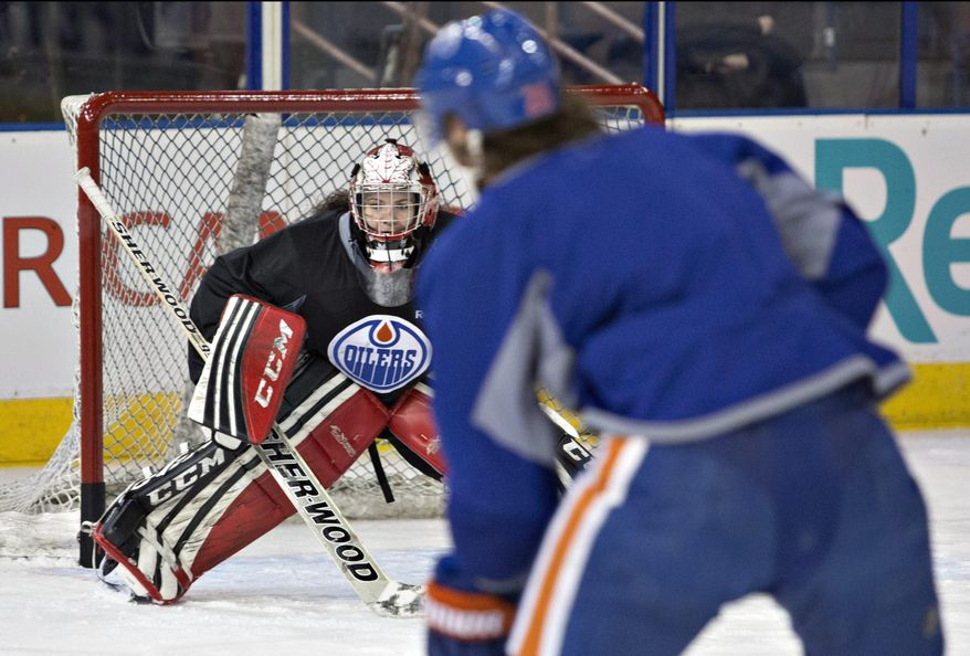Canadian Olympic women's team goaltender Shannon Szabados defends against Edmonton Oilers Ryan Jones as she takes part in the Oilers NHL hockey practice in Edmonton, Alberta, Wednesday, March 5, 2014. (AP Photo/The Canadian Press, Jason Franson)