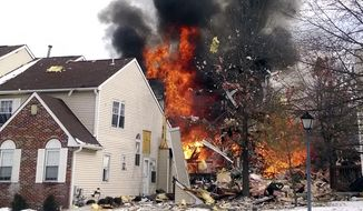 """In this image provided by Josh Forst, flames and smoke shoot up after an explosion at a townhouse complex Tuesday, March 4, 2014, in Ewing, N.J. A gas line damaged by a contractor exploded """"like a bomb"""" while utility crews worked to repair it Tuesday at the complex, injuring at least seven people while several homes were destroyed or damaged.  (AP Photo/Josh Forst)"""