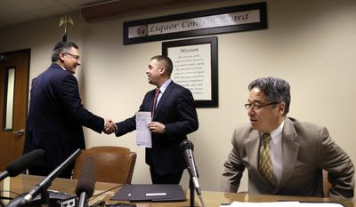 Sean Green, center, is congratulated by Washington State Liquor Control Board Director Rick Garza, left, as board member Chris Marr returns to his seat after Green received his new legal marijuana license Wednesday, March 5, 2014, in Olympia, Wash. Green, a medical marijuana dispensary operator from Spokane, was issued the producer-processor license under the state's recreational pot law at the Liquor Control Board meeting. (AP Photo/Elaine Thompson)
