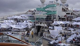 FILE - This Feb. 10, 2013 file photo provided by Kalin Hill, of Houston, shows passengers with makeshift tents on the the deck of the Carnival Triumph cruise ship at sea in the Gulf of Mexico. About three dozen passengers aboard the ill-fated cruise liner have filed a lawsuit in Miami  hoping to collect thousands of dollars as a result of lingering medical and mental issues they claim were caused by their nightmarish experience. (AP Photo/Kalin Hill, File)