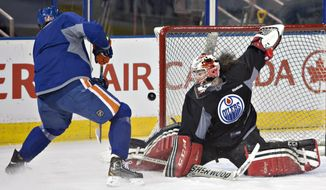 Canadian Olympic women's team goalie Shannon Szabados makes a save on Nail Yakupov as she takes part in the the Edmonton Oilers NHL hockey practice in Edmonton, Alberta, Wednesday, March 5, 2014.  (AP Photo/The Canadian Press, Jason Franson)