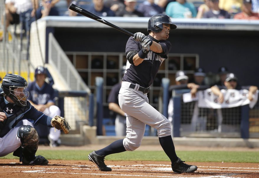 New York Yankees' Ichiro Suzuki, right, singles as Tampa Bay Rays catcher Ryan Hanigan, left, looks on in the first inning of an exhibition baseball game, Wednesday, March 5, 2014, in Port Charlotte, Fla. (AP Photo/Steven Senne)